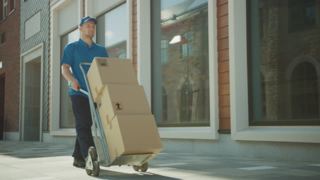 vídeos de stock e filmes b-roll de happy young delivery man pushes hand truck trolley full of cardboard boxes and packages for delivery. professional courier working efficiently and quickly. in the background stylish modern urban area - engradado