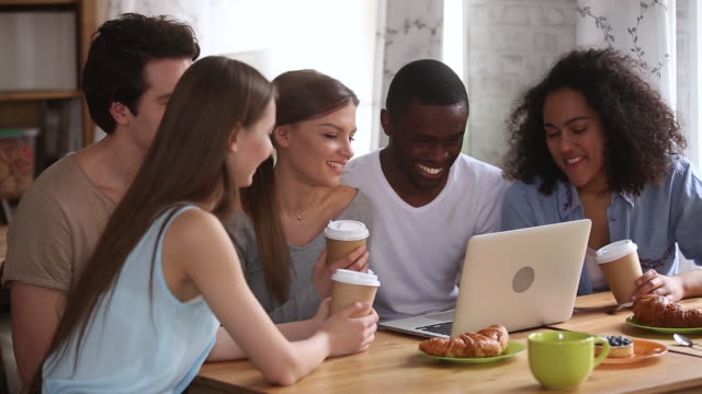 Happy young diverse friends having fun watching comedy on laptop Happy young diverse friends having fun watching comedy movie, online tv show or funny social media video on laptop, multiracial millennial people students group laughing use computer together in cafe mixed race person stock videos & royalty-free footage