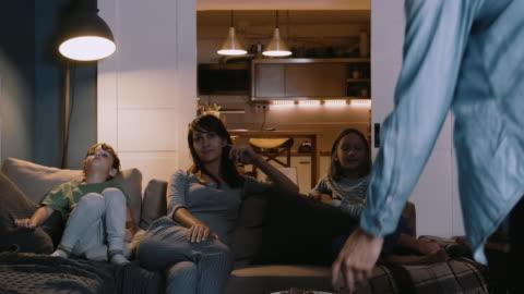 glückliche junge europäische familie mit zwei kindern versammeln sich auf der couch, um zu hause lächelnd fernzusehen. miteinander und unterhaltung. - betrachtung stock-videos und b-roll-filmmaterial