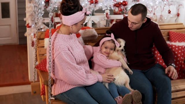 Happy young family at christmas decoration with daughter and dog. Family concept Happy young family at Christmas decoration with daughter and dog. Family sitting on swing near the Christmas tree at porch. Family concept in slow motion. Christmas concept sweatshirt stock videos & royalty-free footage