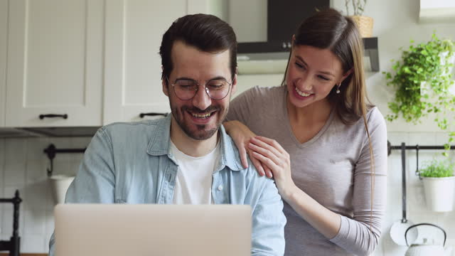 Happy young family couple watching funny video on laptop.