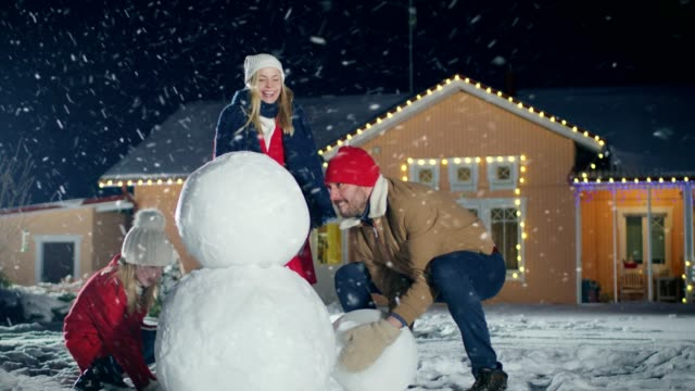 Happy Young Family Making Snowman in the Backyard of their Idyllic House. Father Rolls Snowball and Puts it on top of the Other, Daughter and Wife Help Him. Family Spending Time Together one Winter Evening.