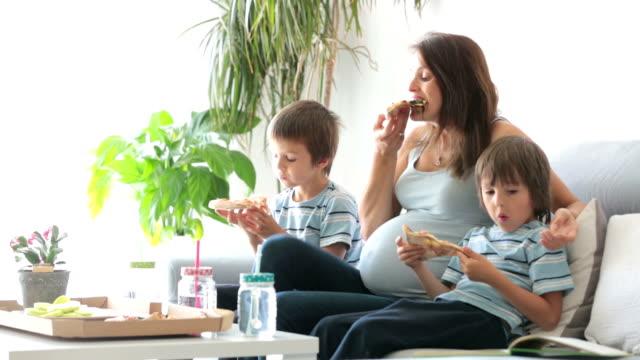vídeos de stock, filmes e b-roll de família jovem feliz, mãe grávida e dois meninos, comendo pizza saborosa em casa, sentado no sofá, lendo um livro e me divertindo - junk food