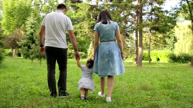 Happy young family teaching baby to walk in the park video