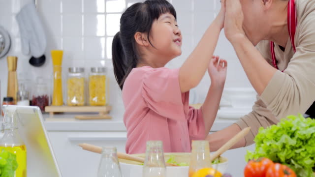 happy young family with dad and young girl cooking in the kitchen preparing a meal together.modern families - padre single video stock e b–roll