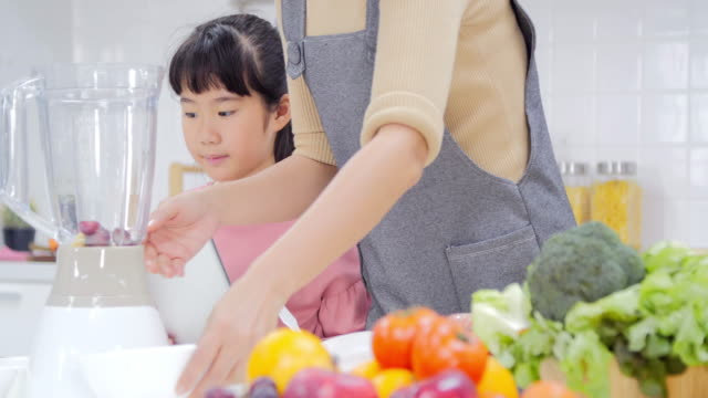 vidéos et rushes de heureux jeune famille avec maman, jeune fille de cuisine dans la cuisine à préparer un repas ensemble - seulement des japonais