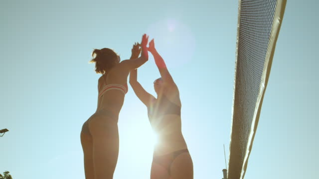 SLOW MOTION: Happy young female volleyball players celebrate scoring a point. SLOW MOTION, LOW ANGLE, CLOSE UP, LENS FLARE: Happy young female volleyball players celebrate scoring a point. Cheerful women on holiday high fiving and fist bumping while they play beach volleyball. volleyball sport stock videos & royalty-free footage