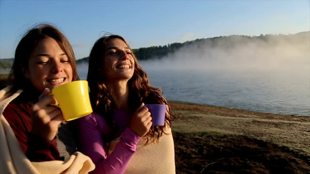 happy young females drinking tea near amazing beautiful foggy lake - tea cup stock videos & royalty-free footage