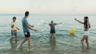 istock Happy Young Friends Dancing in the Sea with Sparklers 1163205914