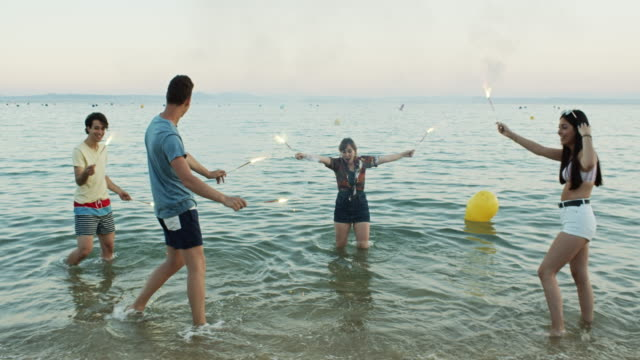 Happy Young Friends Dancing in the Sea with Sparklers