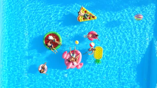 vídeos de stock, filmes e b-roll de aéreos felizes jovens amigos jogando com uma bola diversão coloridas boias na piscina - inflável