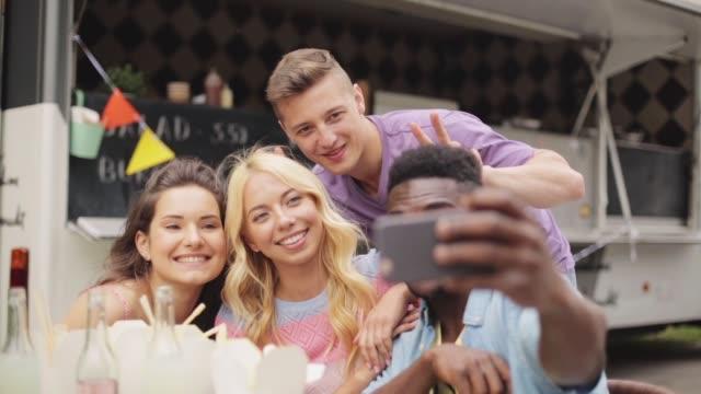 stockvideo's en b-roll-footage met happy jonge vrienden op food truck selfie te nemen - foodtruck