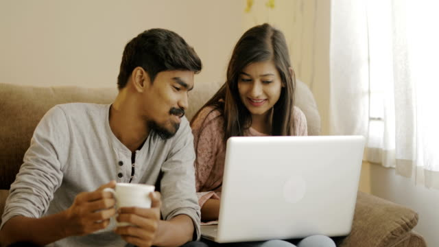 Happy young friends using laptop Happy young friends using laptop on sofa at home. indian culture stock videos & royalty-free footage