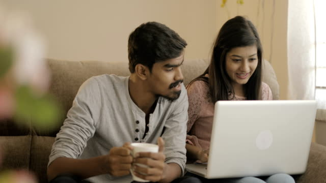 Happy young friends using laptop Happy young friends using laptop on sofa at home. indian subcontinent ethnicity stock videos & royalty-free footage