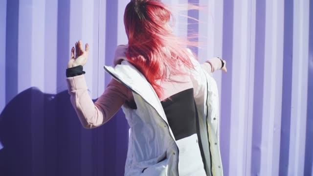 stockvideo's en b-roll-footage met gelukkige jonge funky vrouw met roze haar dansen op gekleurde achtergrond. mooie vrouw dansen in slow motion - roze haar