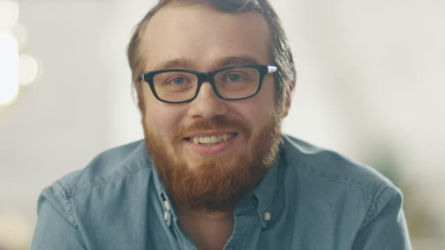 Happy Young Ginger Bearded Man Wearing Glasses Smiles Into the Camera. Bright Lights In the Background. video