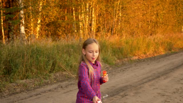 Happy young girl blowing soap-bubbles, twisting and turning around. Outdoor autumn. Slow motion video