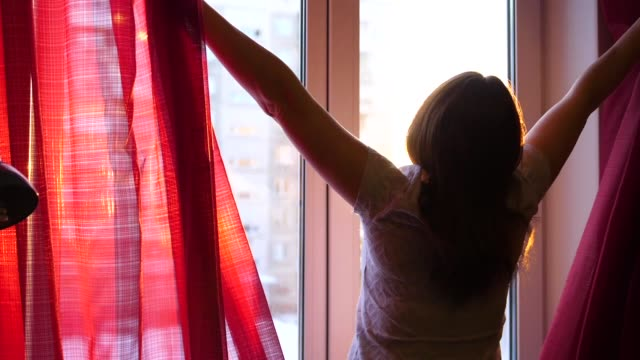 Happy young girl coming to the window, opens the curtains. The sun's rays pass through the window, illuminating the room and the girl. Sunset time The sun's rays pass through the glass and illuminate the room with morning light. Girl goes early morning to the window, opens the curtains. light natural phenomenon stock videos & royalty-free footage