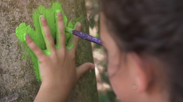 木アート木スローモーションの下の公園で屋外で遊ぶ子供たちの外にカラフルな絵の具で手形を残して夏キャンプで幸せな若い女の子 ビデオ