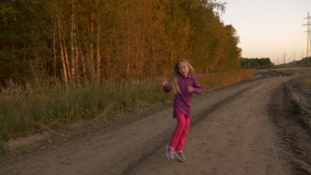 Happy young girl play at country road and show thumbs up gestures. White girl jumping up at sunset. video