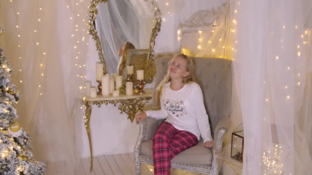 Happy young girl sitting in armchair. Happy young girl sitting in armchair. Beautiful teenage girl looking around while sitting in armchair in Christmas eve. Christmass New Year decorated interior tulle netting stock videos & royalty-free footage