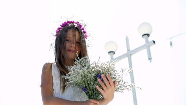 Happy young girl sniffing flowers in hands and smiling at bay bar. Slowly video
