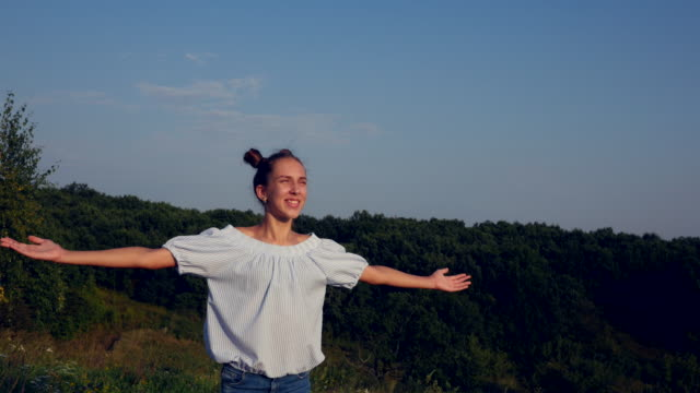 Happy young girl standing in nature with arms spread open, enjoying the rays of sunset video