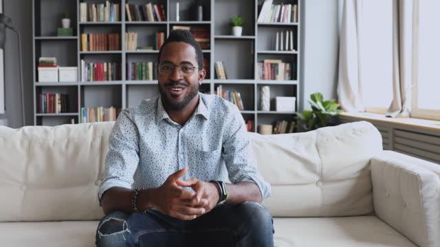 vídeos de stock, filmes e b-roll de feliz jovem e bonito blogueiro afro-americano gravando vídeo. - discurso