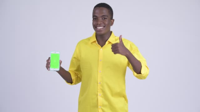 Happy young handsome African businessman showing phone