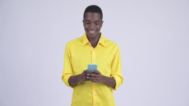 Feliz jovem homem de negócios africano bonito usando telefone - vídeo
