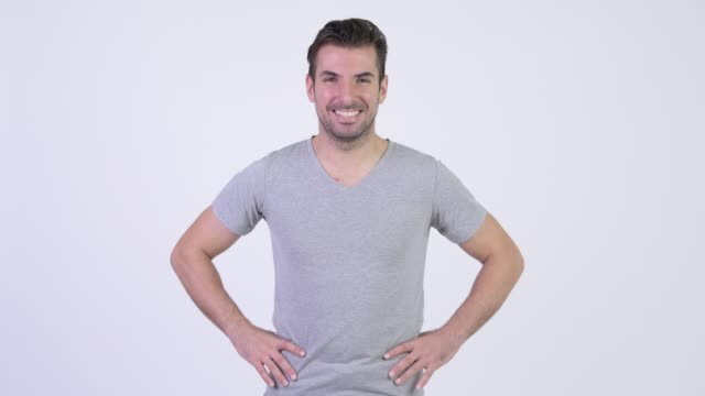 Happy young handsome Hispanic man smiling Studio shot of young handsome Hispanic man against white background arms akimbo stock videos & royalty-free footage