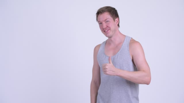 Happy young handsome man showing something to the back Studio shot of young handsome Scandinavian man against white background tank top stock videos & royalty-free footage