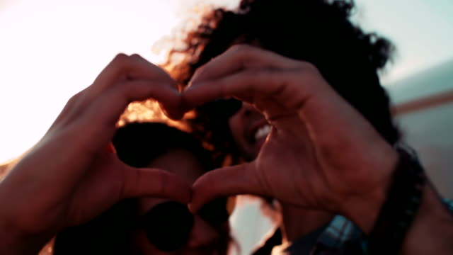 Happy young hipster couple making heart shape with hands