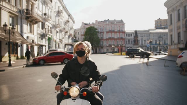 vídeos de stock e filmes b-roll de happy young hipster couple riding a vintage scooter in city in protective masks during pandemia of covid-19, slow motion, tracking shot - covid hair