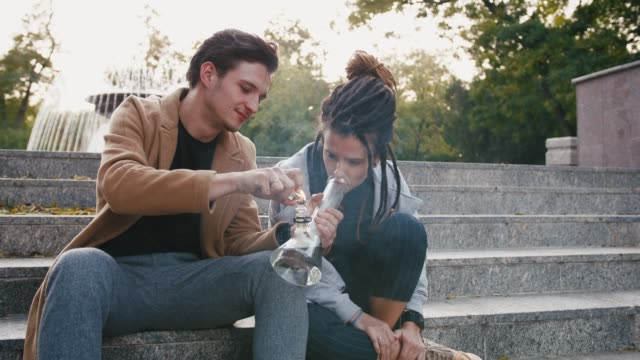 happy young hipster couple sitting on stairs and smoking weed with a bong in park, slow motion - дикая растительность стоковые видео и кадры b-roll