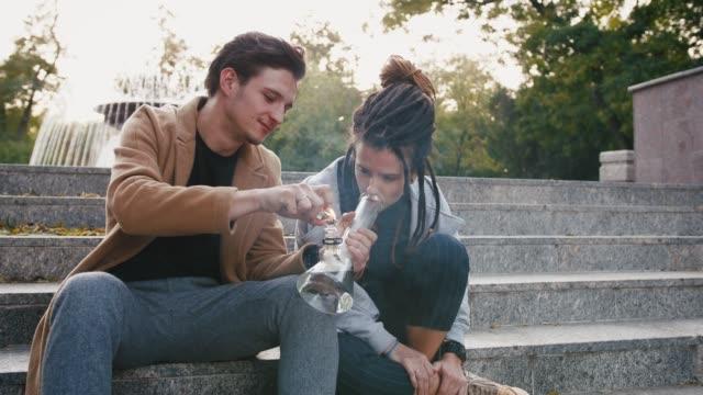 stockvideo's en b-roll-footage met gelukkig jong hipster paar zittend op trappen en roken van onkruid met een bong in park, slow motion - niet gecultiveerd