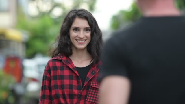 happy young hipster woman greeting young man outdoors - machać filmów i materiałów b-roll