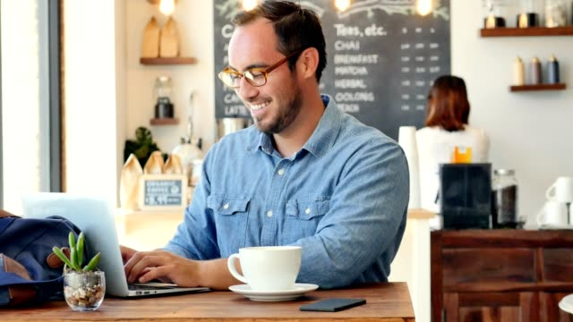 happy young hispanic man smiles while using computer in coffee shop - biznes finanse i przemysł filmów i materiałów b-roll