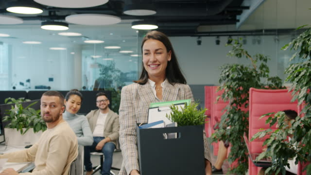 Happy young lady former employee quitting job leaving office room with box of things