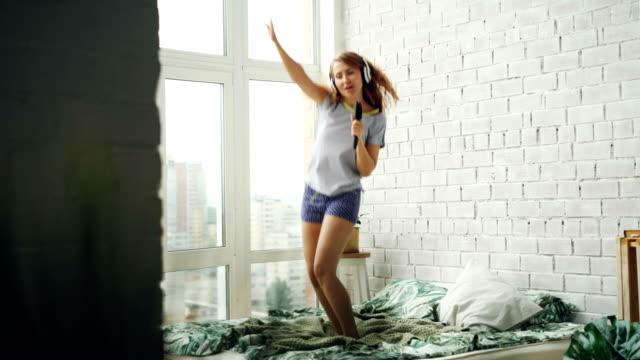 幸せな若い女性が楽しんでヘアブラシで歌やダンスの家庭での余暇時間中にヘッドフォンで音楽を聞きながら、ベッドにジャンプします。若さと喜びのコンセプトです。 - ブラシ点の映像素材/bロール
