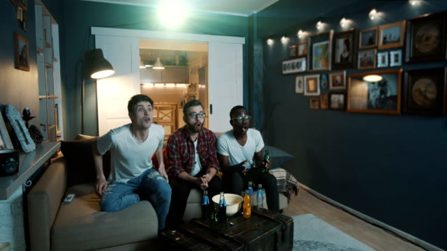 Happy young male friends watch sports game on TV at home with projector, shout supporting favourite team slow motion. video