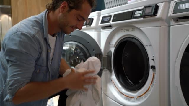 Heureux jeune homme à une laverie automatique, machine à laver de chargement - Vidéo