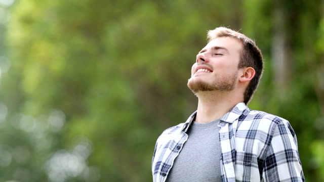Happy young man breathing deep outdoors Happy young man breathing deep with a green forest in the background deep stock videos & royalty-free footage