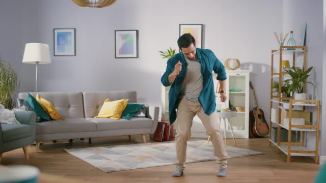 행복 한 젊은 남자는 거실 중간에 춤. 재미 있은 남자 창조 하 고 전문적으로 춤을 집에서. - 댄싱 스톡 비디오 및 b-롤 화면