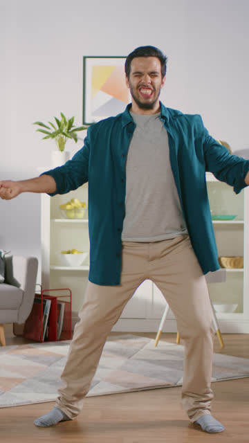 happy young man dances in the middle of the living room. funny man creatively and professionally dances at home. video footage with vertical screen orientation - вертикальный стоковые видео и кадры b-roll