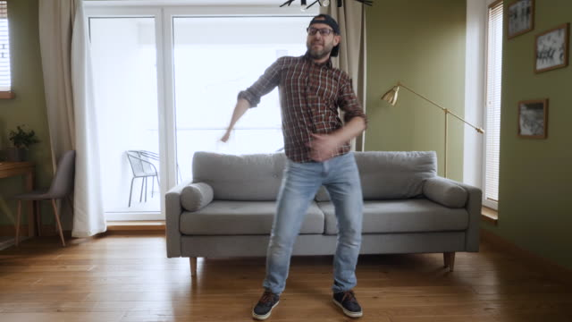 stockvideo's en b-roll-footage met happy young man dancing at home living room, fun celebrating funny viral dance freedom weekend. guy geniet van dans, plezierfeest. vrolijke mens die vrolijk in woonkamer danst. slow motion. - youtube