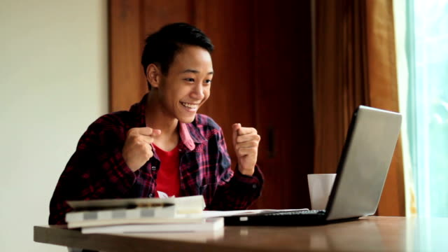 Happy young man feeling excited see good news from laptop at home Happy teenage boy feeling excited to see a good news in email from laptop at home. online study, learning success, global education and e-leaning concept. educational exam stock videos & royalty-free footage