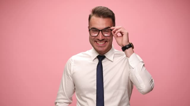 happy young man in white shirt wearing glasses smiling, laughing and looking over glasses on pink background