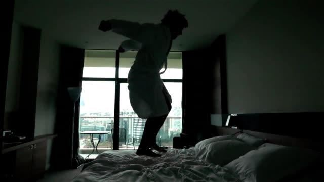 vídeos y material grabado en eventos de stock de feliz joven saltando en la cama del hotel en albornoz - cómodo conceptos