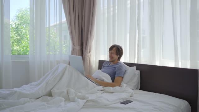 침대에 누워 행복한 청년이 화상 회의를 통해 누군가에게 이야기합니다. covid 사회 비탄화. 새로운 정상. 연결된 개념 유지 - 한 명의 중년 남자만 스톡 비디오 및 b-롤 화면